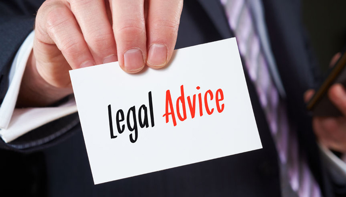 "A close up of a hand holding a white piece of paper that says ""Legal Advice"" in black and red"